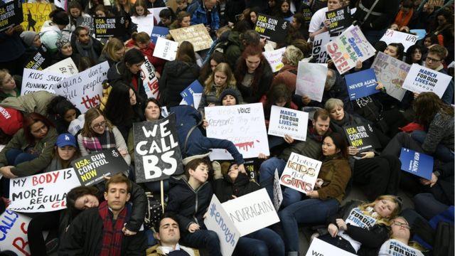 """Присталице строже контроле оружја седе и леже на улици испред америчке амбасаде у Лондону у оквиру """"Марша за наше животе"""""""