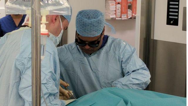 د احمد يجري العملية مستخدما النظارة للتصوير
