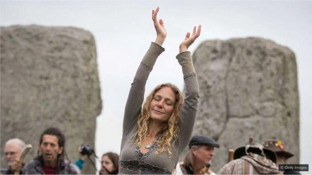 Une femme danse alors que druides, païens et fêtards se rassemblent à Stonehenge