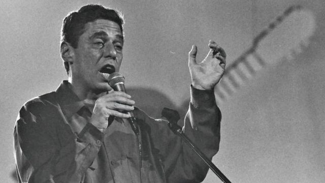 Chico cantando ao microfone em foto preto e branca