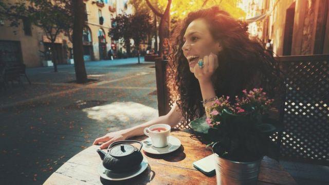 Una mujer sonriente sentada a la mesa, en un café (y con un café)