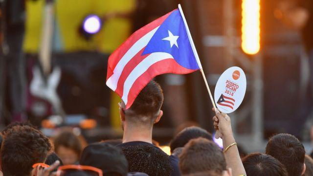 Grupo de personas y una bandera de Puerto Rico