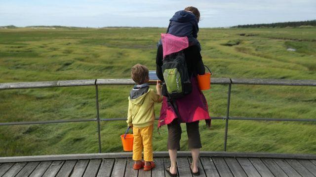 Mulher passeia com crianças no gramado