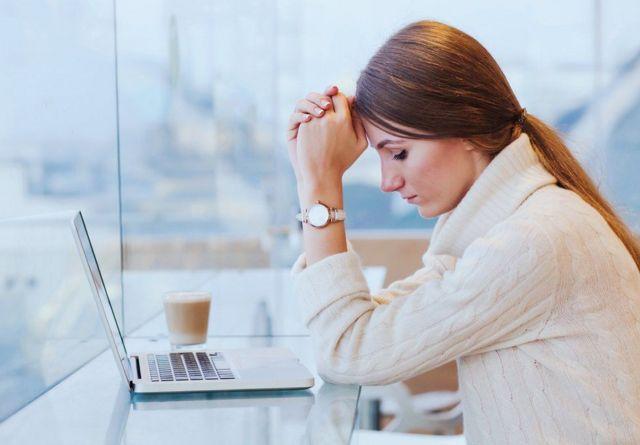 컴퓨터 앞에서 머리를 감싸쥐고 있는 여성