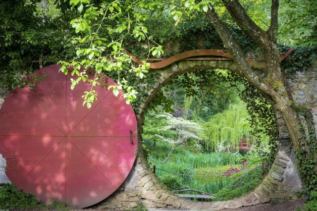 A circular doorway looking onto a green landscaped garden