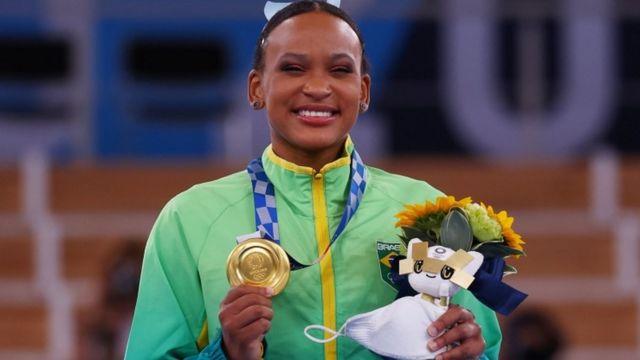 Rebeca posa com medalha de ouro em pódio