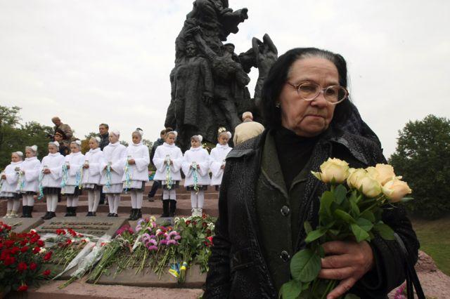 Жінка біля пам'ятника у Бабиному Яру