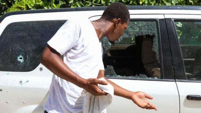 Un hombre junto a un auto baleado