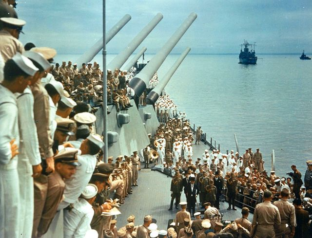 Soldiers and sailors on the decks of the USS Missouri watch representatives from Japan formally surrender