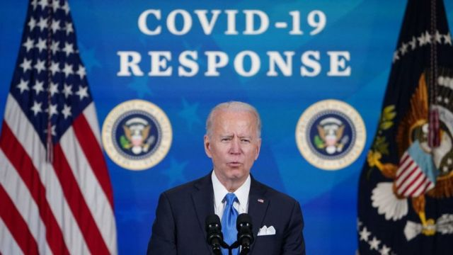 Biden with a sign in the background: response to covid-19