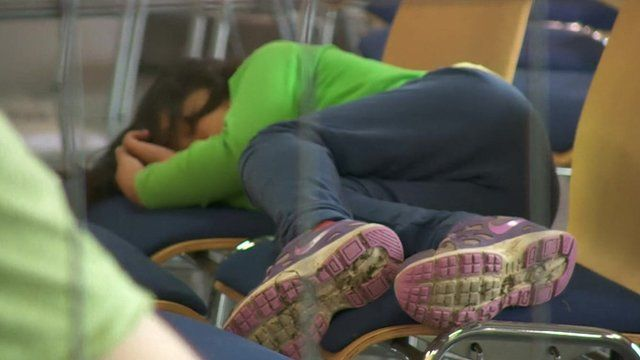 A young asylum seeker sleeping on wooden chairs.