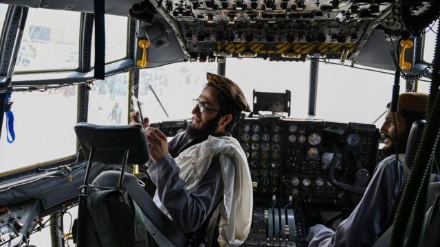 Anggota Taliban di pesawat milik Angkatan Bersenjata Afghanistan setelah AS menarik diri.