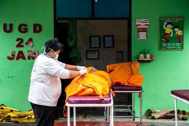 Seorang perempuan memeriksa salah satu kantong jenazah korban tsunami Selat Sunda (24/12). Lebih dari 400 orang tewas tersapu gelombang tsunami yang menerjang pesisir Banten dan Lampung 22 Desember lalu.