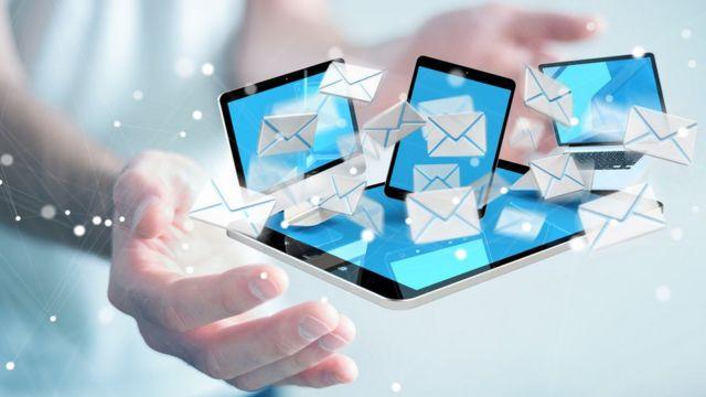 Mão segura telas de celulares com várias correspondências que simbolizam e-mails
