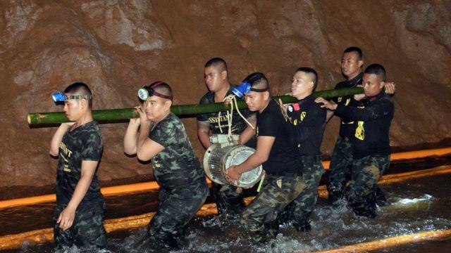 Homens de equipe de resgate carregam equipamentos nos arredores de caverna na Tailândia, onde meninos estavam presos