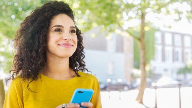 Mujer con celular mirando el horizonte