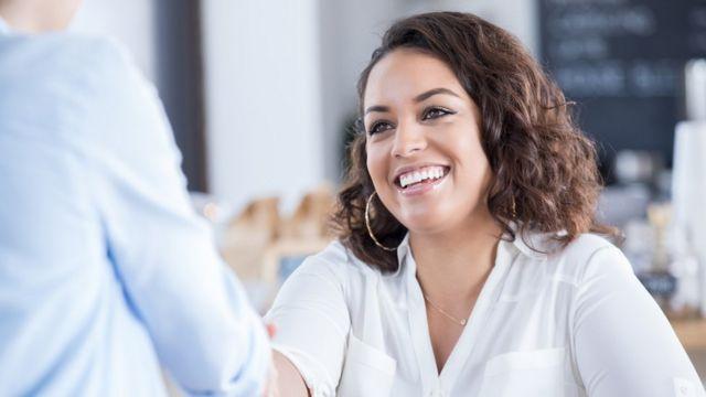 Mujer saludando a una persona en oficina.