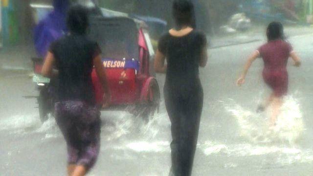 People walking through flood water