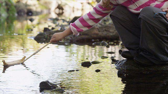 """Criança brinca com barquinho em jardim da infância florestal, em cena do documentário """"Nature Play"""""""