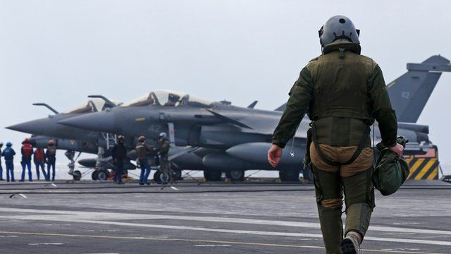 A pilot walks to his Rafale fighter jet prior to a mission in the Gulf aboard France's Charles de Gaulle aircraft carrier.