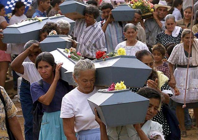 Mujeres cargan ataúdes con restos de las víctimas de la masacre de El Mozote.