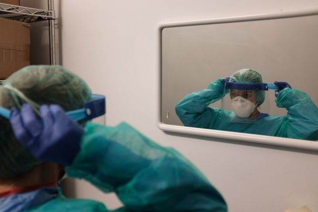 A hospital worker puts on a protective visor