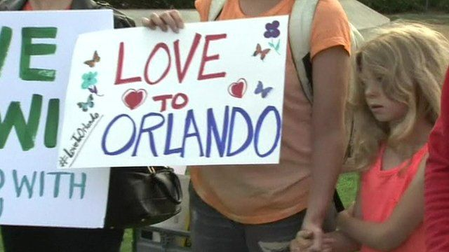 Girl and parent with a sign saying Love to Orlando