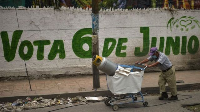 A man walks past a sign encouraging voting in the Mexican elections.