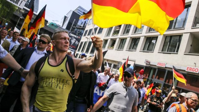 """A protester waves the german flag during the right-wing AfD Alternative for Germany political party demonstration titled """"Future Germany"""" on May 27, 2018 in Berlin, Germany."""