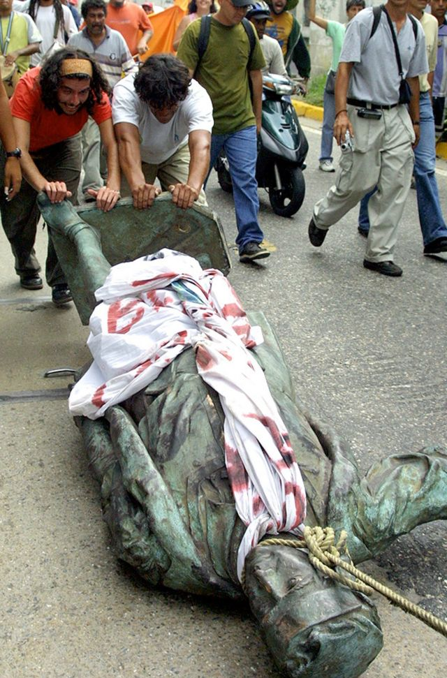 Varias personas arrastra la estatua de Colón