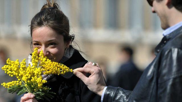 Dünya Kadınlar Günü 2012: İtalya'nın başkenti Roma'da bir kadın mimoza buketi tutuyor.