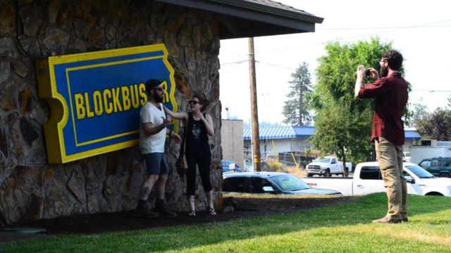 Turistas se toman fotos en el aviso del último Blockbuster.