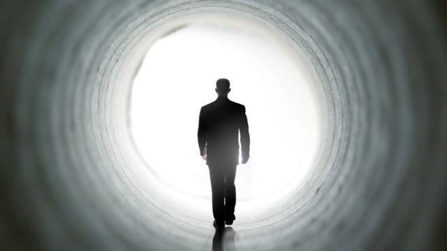 Sombra de homem caminha em direção a luz em um túnel