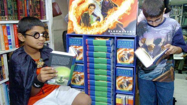 """Deux garçons indiens, portant des t-shirts et des robes Harry Potter, lors du lancement de """"Harry Potter et le Prince de Sang-Mêlé"""" à un stand de livres à New Delhi, le 16 juillet 2005."""