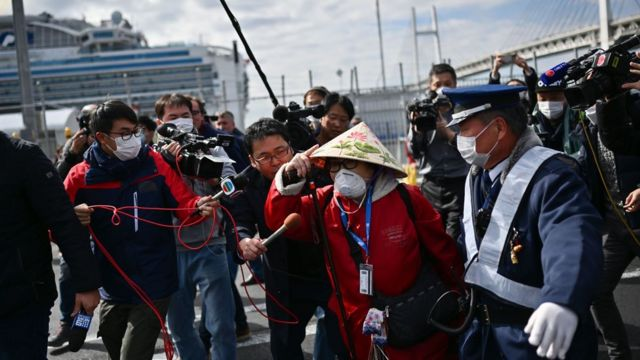 A passenger (centre R) leaves on foot after disembarking the Diamond Princess cruise ship in quarantine due to fears of the new COVID-19 coronavirus, at the Daikoku Pier Cruise Terminal in Yokohama on February 19, 2020.