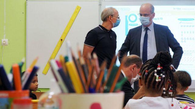 O ministro de educação da França, Jean-Michel Blanquer, de máscara, em frente à um telão na sala de aula
