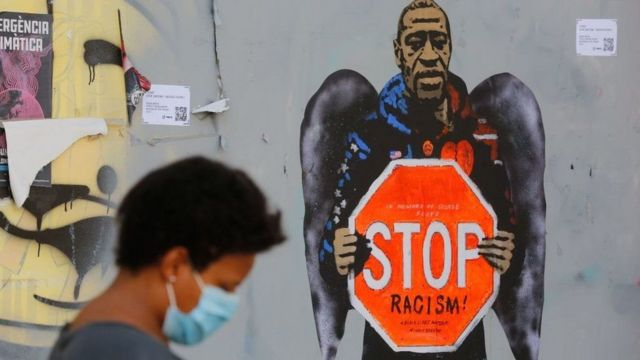 A graffiti with the image of George Floyd holding a traffic sign that says
