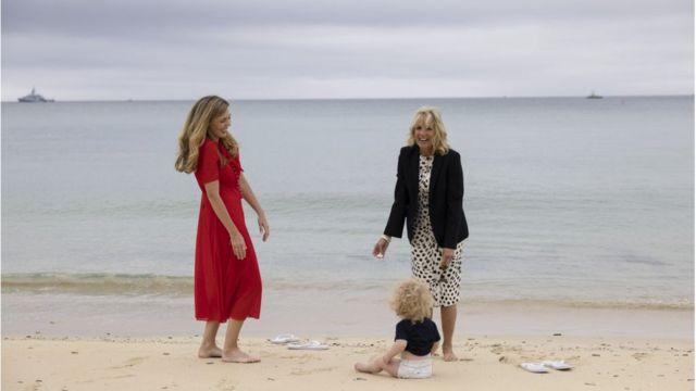 拜登夫人和约翰逊夫人在卡比斯湾的沙滩上脱掉鞋子在海滩陪伴约翰逊夫妇的儿子。