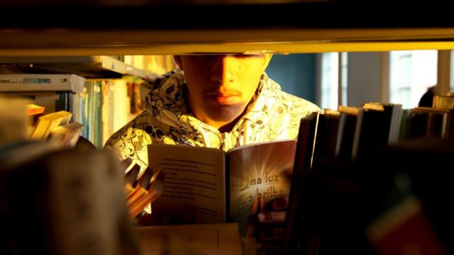 Menino olha para livro na biblioteca