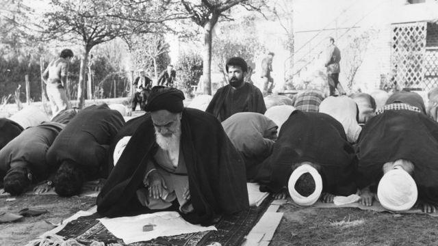 Khomeini prie dans le jardin de sa maison en exil en France.
