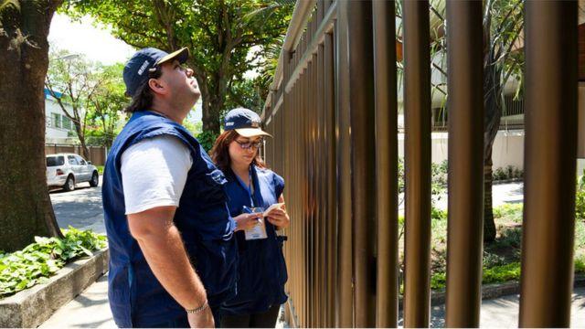 Dois agentes do censo em frente a um portão de prédio