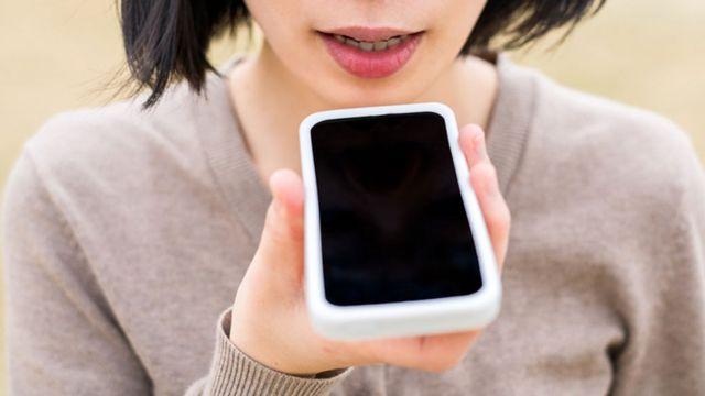 Joven hablando a un celular en su mano
