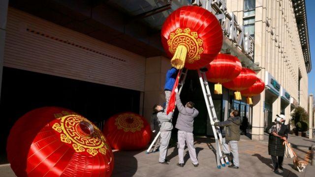 Hombres colgando lámparas rojas en Pekín, el 31 de diciembre.