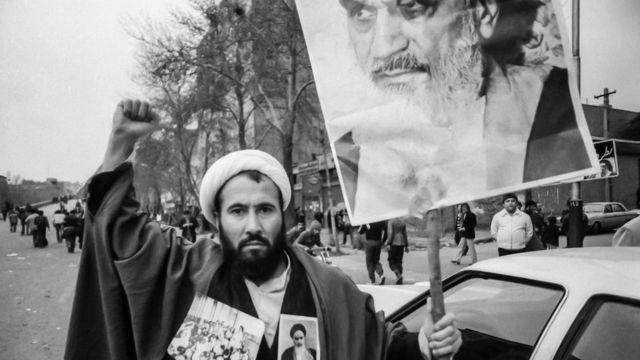 Um clérigo xiita segura uma faixa mostrando o aiatolá Ruhollah Khomeini durante a Revolução Islâmica do Irã de 1979