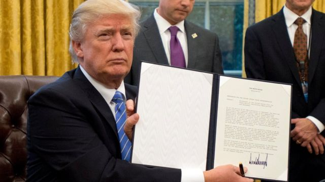 Trump con una orden ejecutiva firmada.