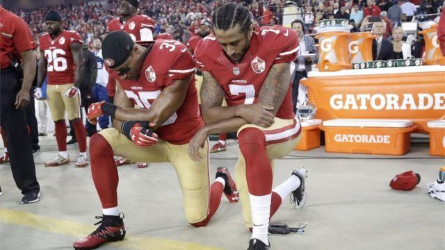 Eric Reid et Colin Kaepernick mettant un genou au sol durant l'hymne national américain
