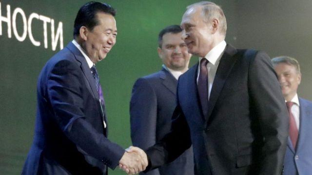 Президент Интерпола Мэн Хунвэй и президент России Владимир Путин на конференции по кибербезопасности в этом году в Москве