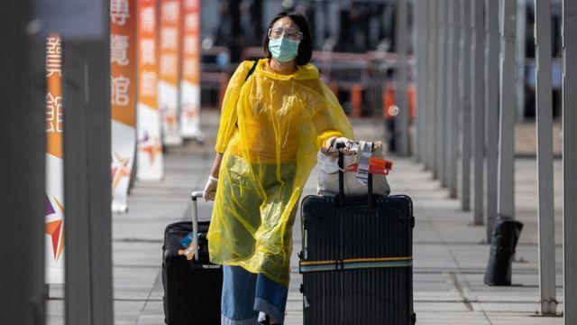 香港國際機場亞洲國際博覽館一名抵港女士拉著行李離開檢疫中心(16/4/2020)