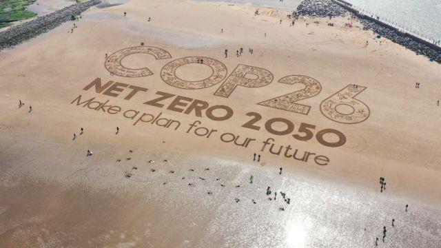 Imagem gravada na areia de uma praia na Inglaterra que diz 'COP 26, emissões líquidas zero em 2050, façam um plano para o nosso futuro'