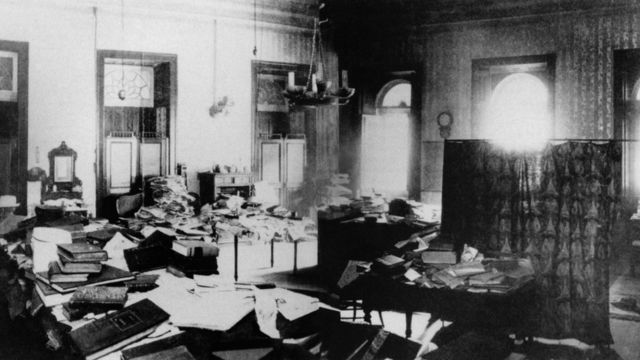 Foto antiga mostra livros e papéis espalhados por cômodo